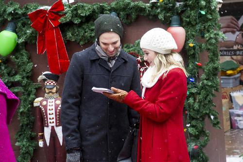 A man and woman stand in the snow looking at a notepad