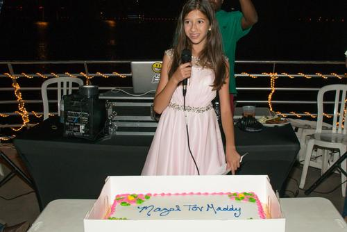 "Maddy Pollack speaking at her Bat Mitzvah party, microphone in hand. Cake on a table in front of her with text ""Mazel Tov, Maddy."""