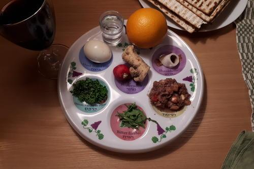 A seder plate with the six traditional items and an orange.