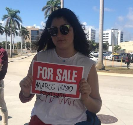 "Lila Goldstein holding a sign that reads ""For Sale: Marco Rubio"""