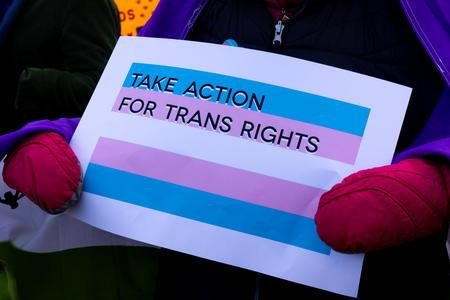 "A person holds a sign reading ""Take Action for Trans Rights."""