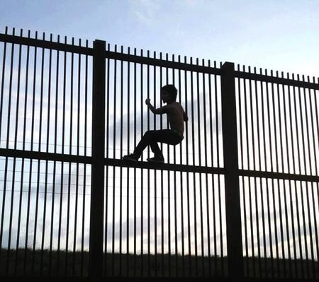 A Child Climbing a Fence at Mexico-US Border Cropped